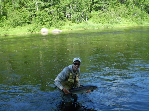 Stephen Miller releases a 12 pound salmon on the Northwest Miramichi Monday, July 2, 2012.